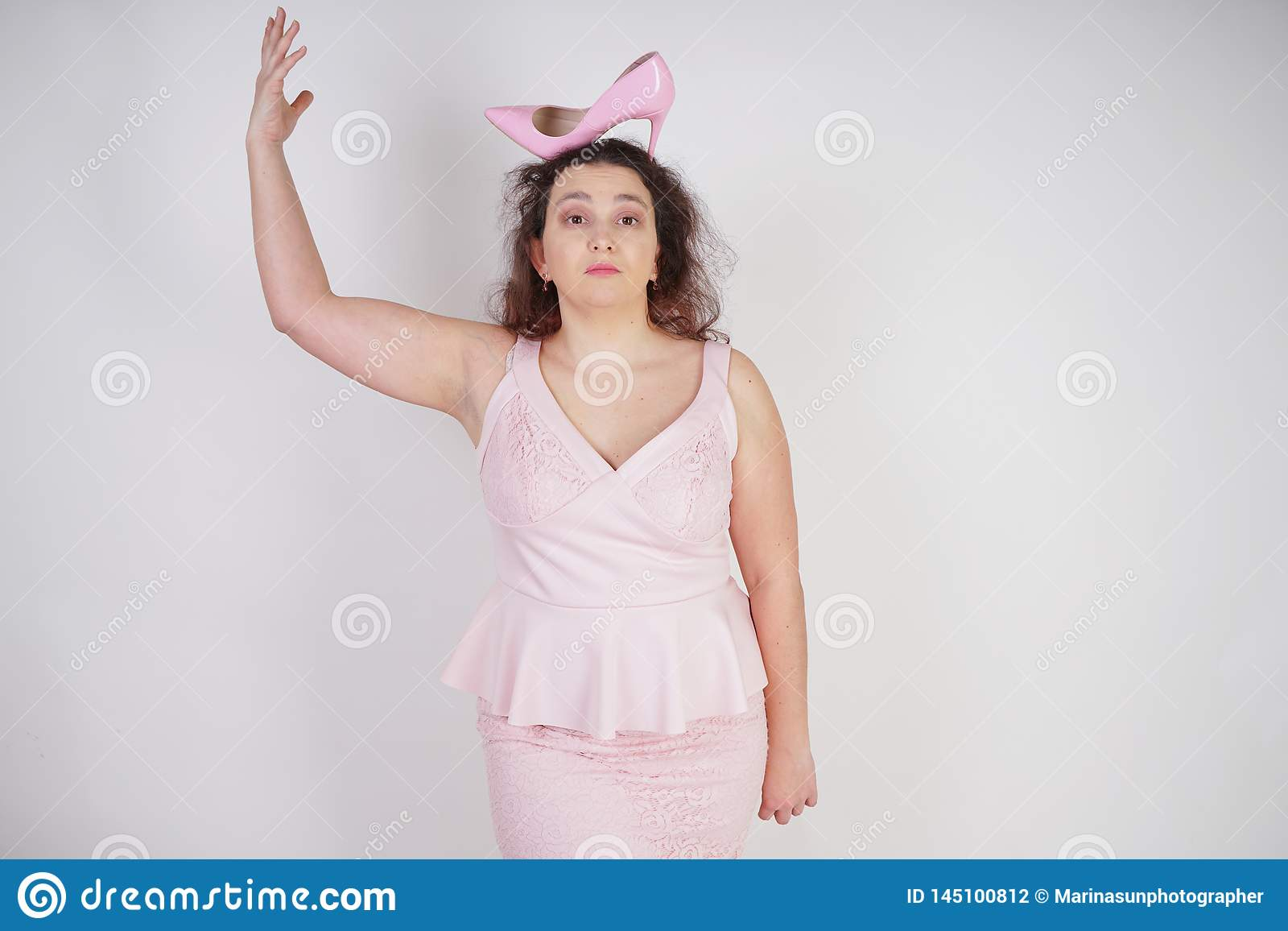 Pretty plump woman in pink dress with patent leather stiletto heels on white background in Studio