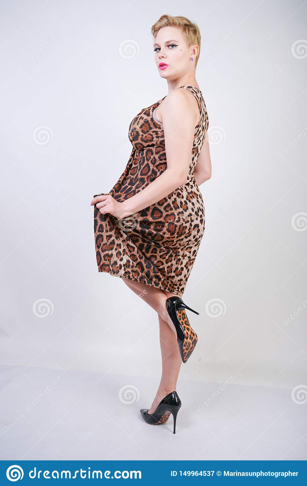 Pretty plus size young woman with short blonde hair wearing middle length summer dress with animal leopard print. cute curvy woma