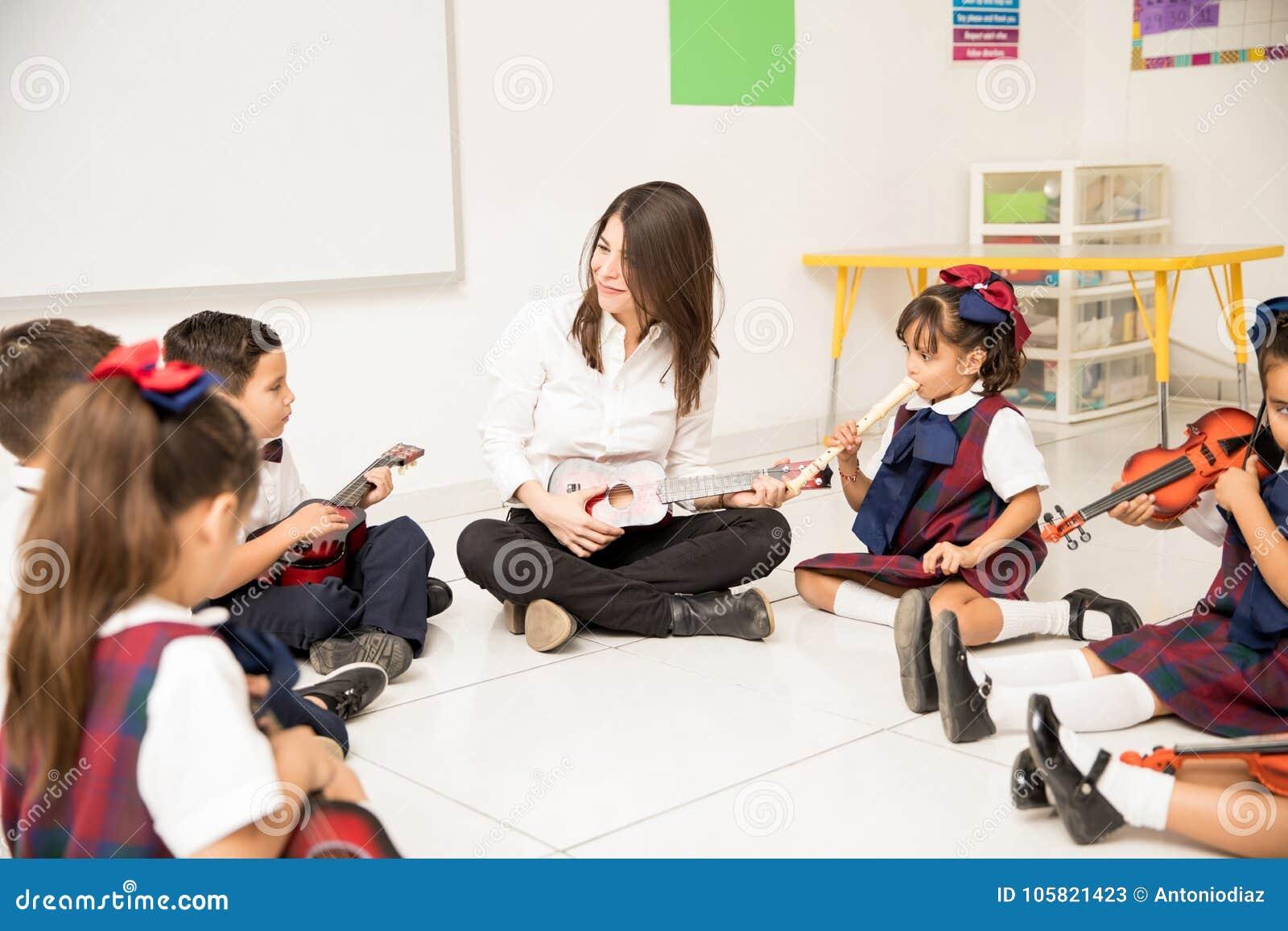 happy music teacher in preschool stock image