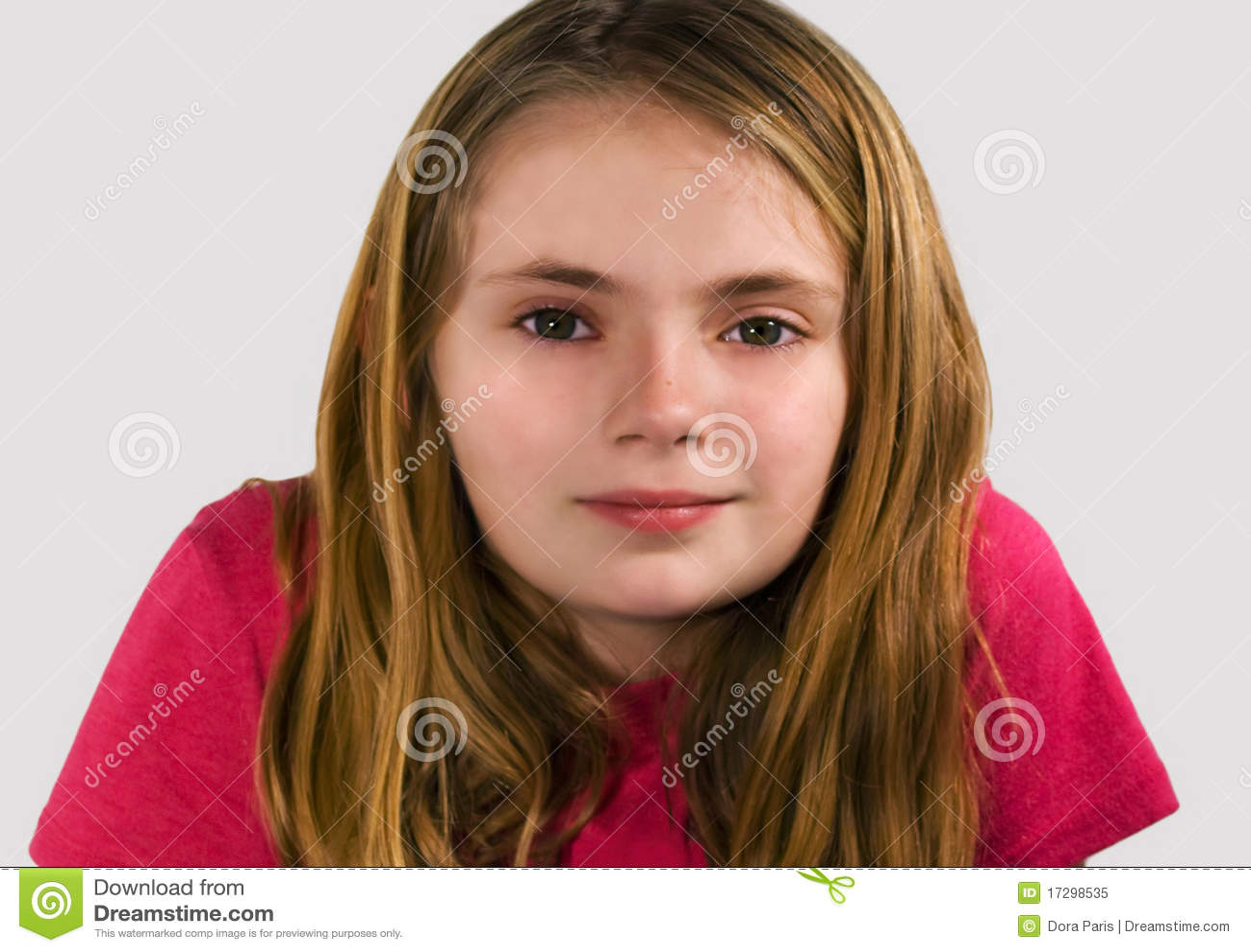 Soft focus portrait of pretty preteen girl smiling at camera.