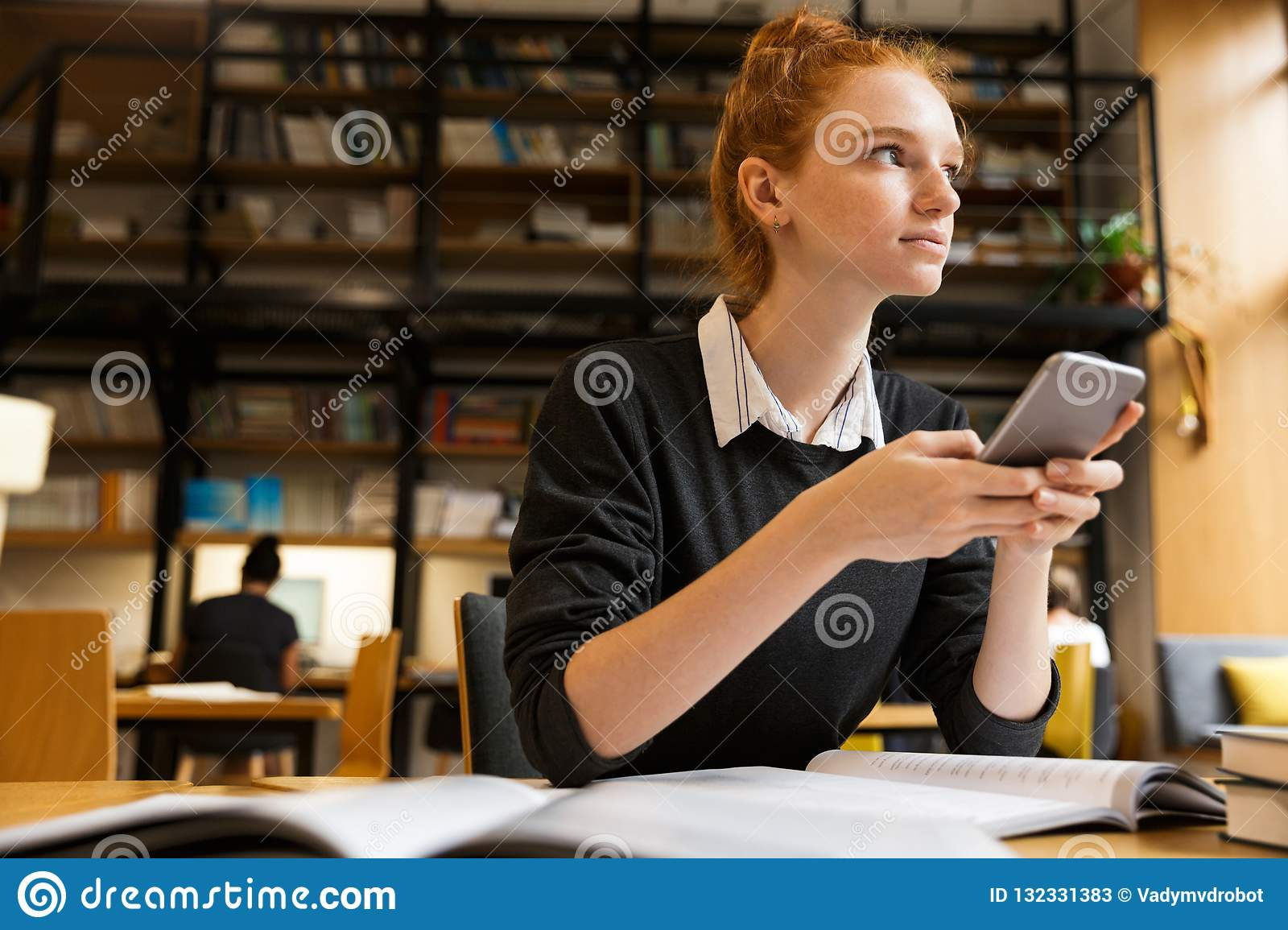 Pretty red haired teenage girl studying at the table