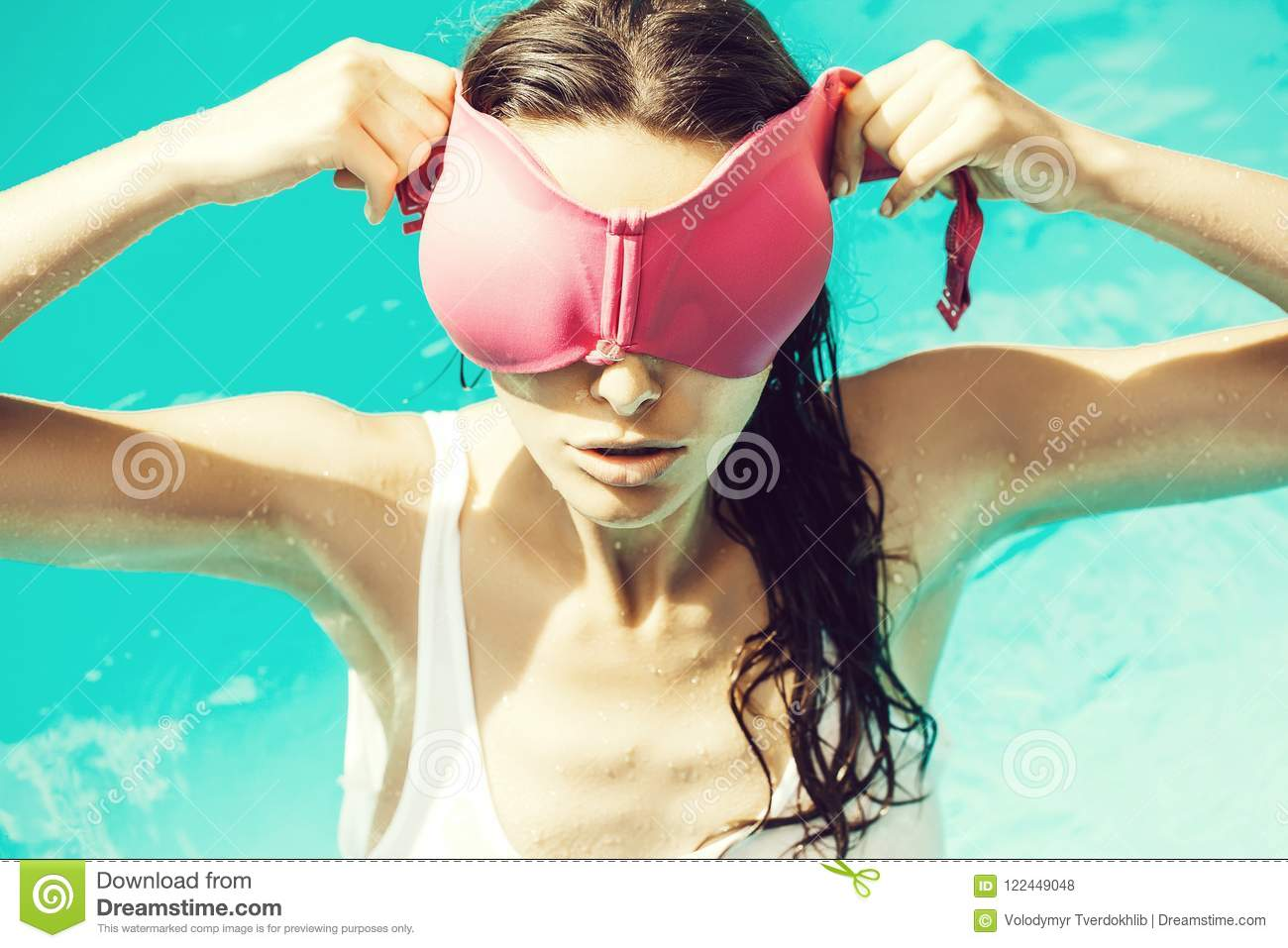 a9fa704c7cd33 Young pretty woman or girl with long wet hair in swimming pool with blue  water sunny summer day outdoor holding pink swimsuit bra on face.