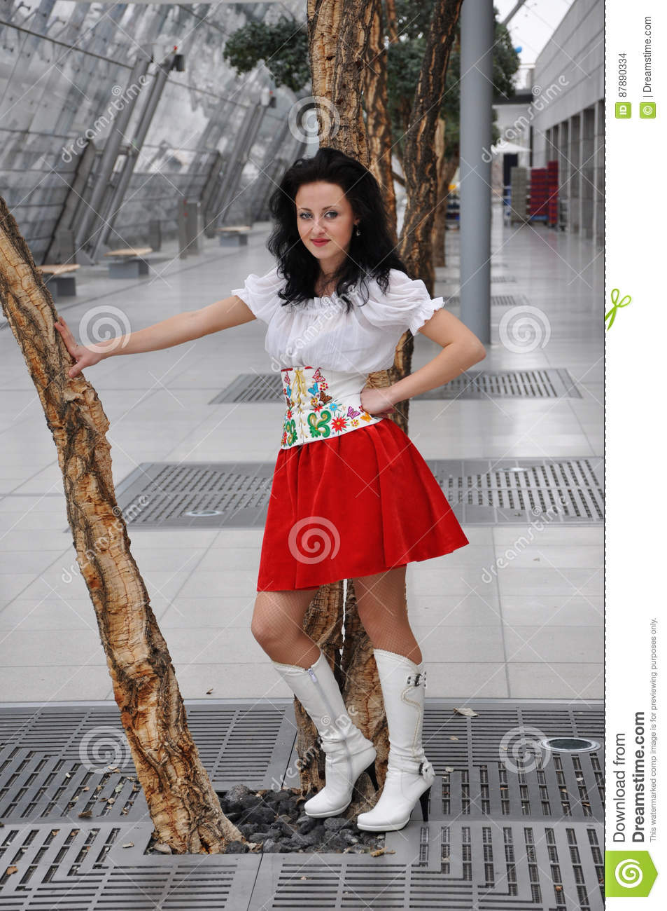 Pretty woman or cute girl with adorable smiling face in national ukrainian  embroidered belt, red skirt and white blouse, boots near tree, has long  brunette ...