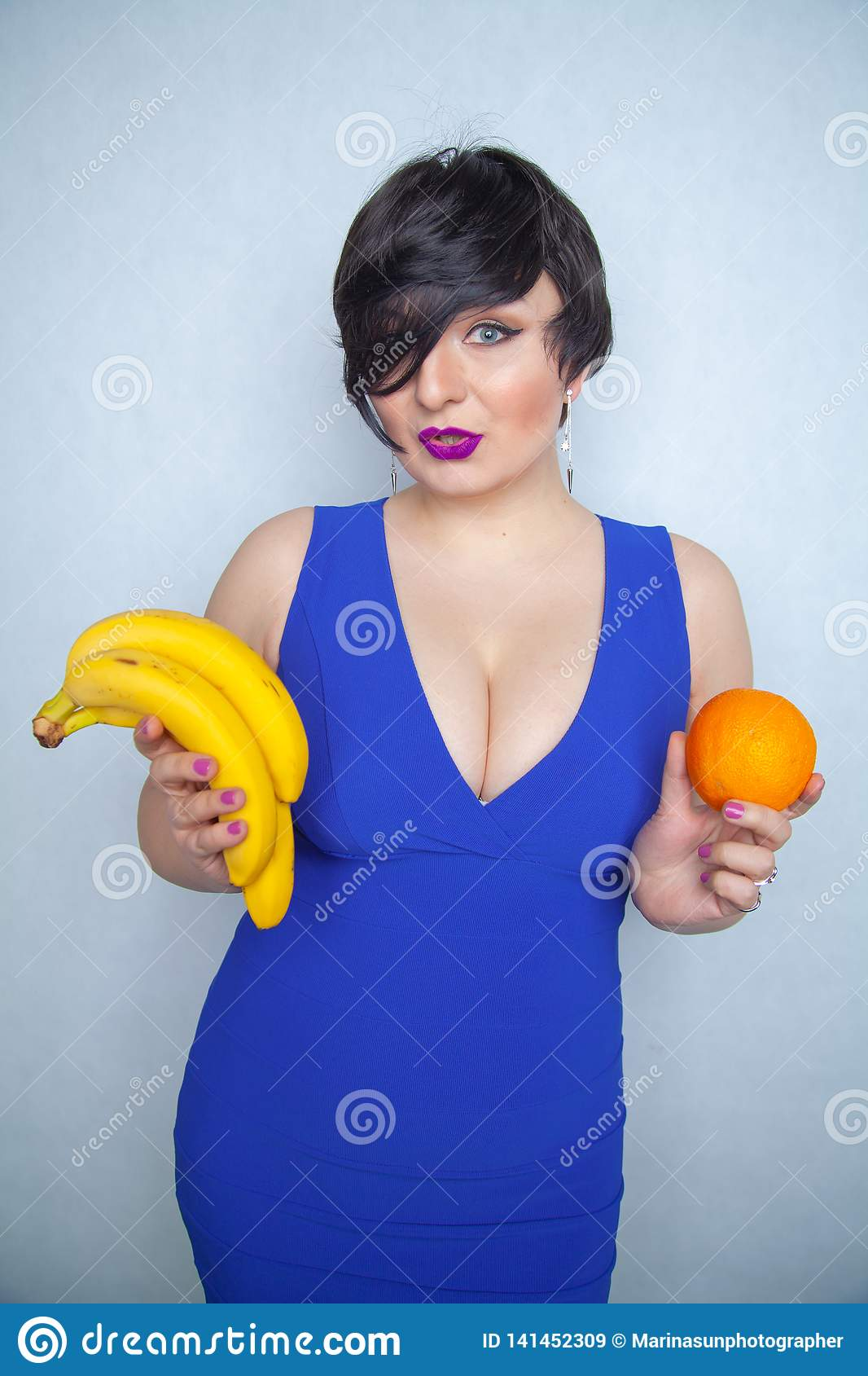 Cute Chubby Girl With Short Black Hair In A Blue Dress Holding An Orange And Bananas -1526