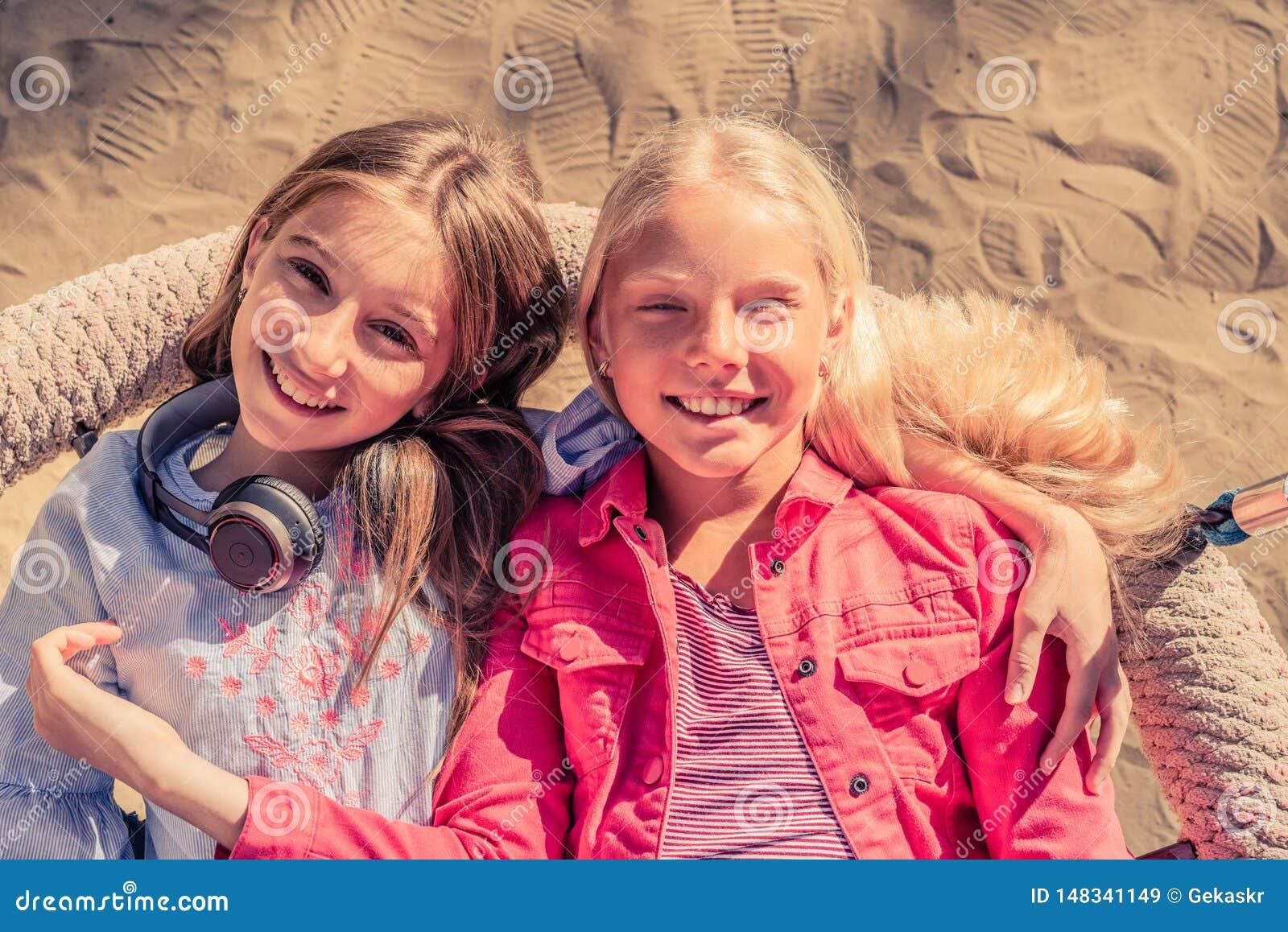 Pretty smiling teenage girls sit lying together