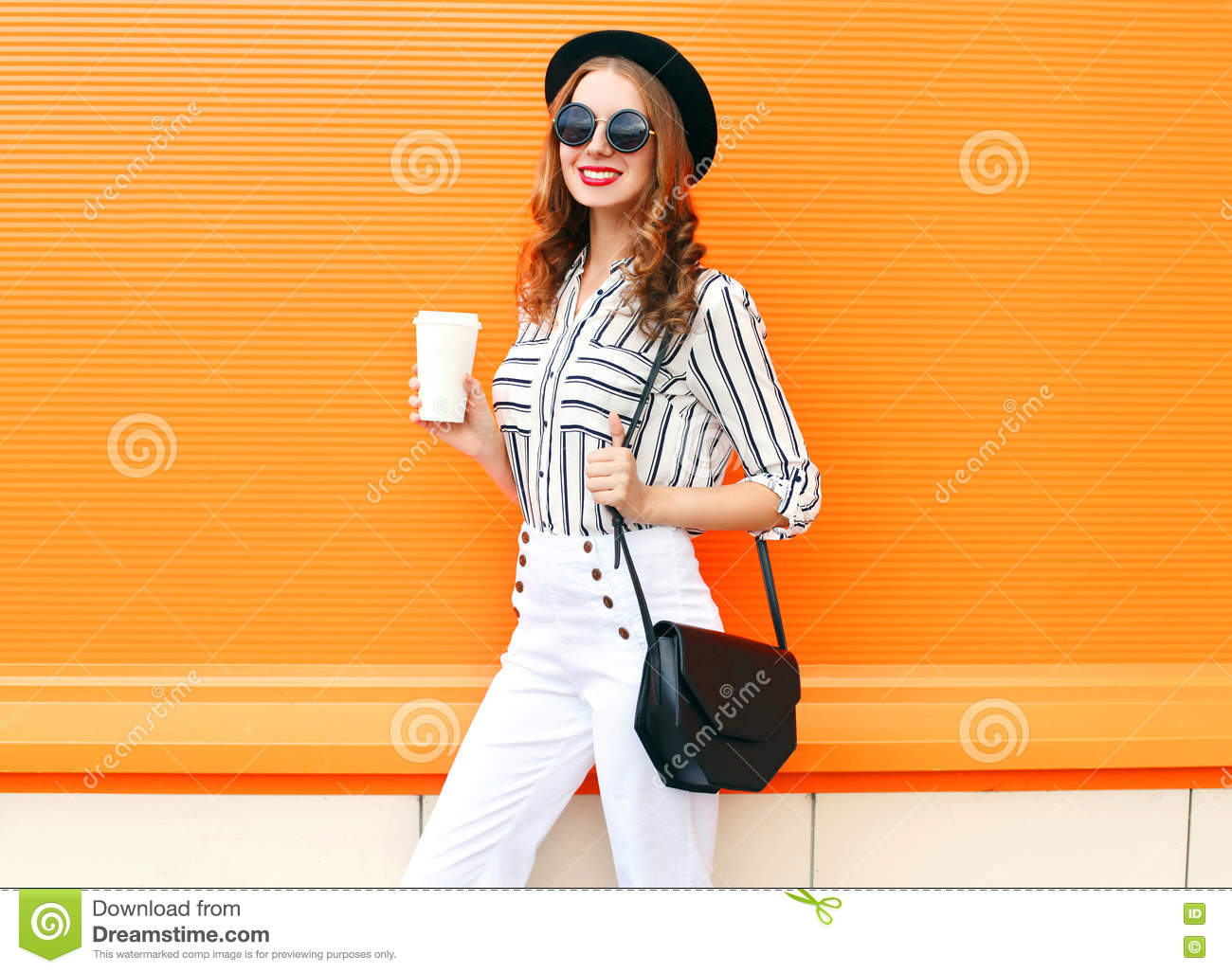 Pretty smiling woman with coffee cup wearing fashion black hat white pants handbag clutch over colorful orange