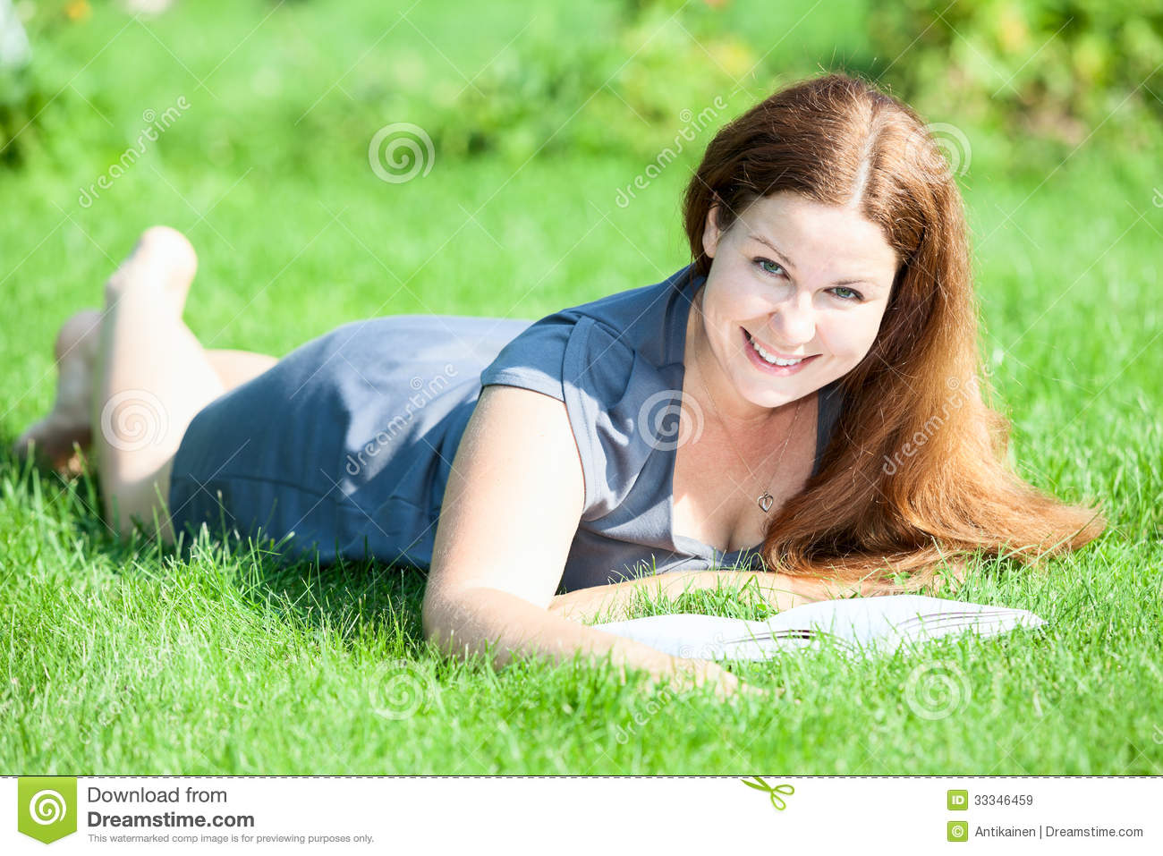 Pretty smiling woman lying on green grass with book for Pretty grass