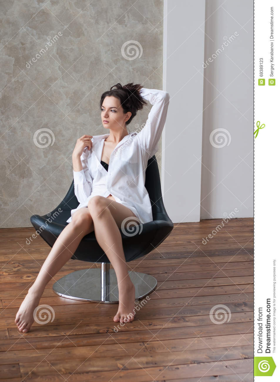 pretty sociable female in white shirt sitting on armchair stock image