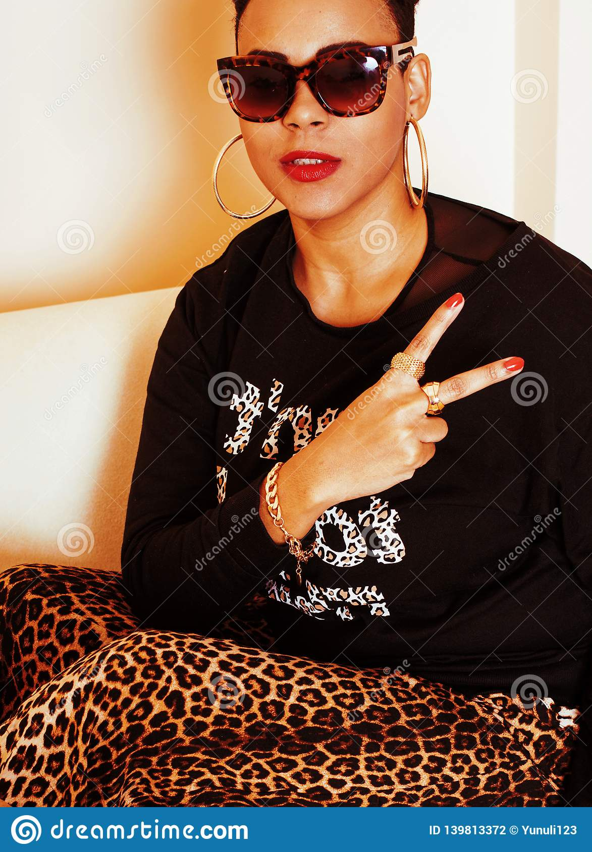 Pretty stylish african american big mama woman well dressed. swag relax at home, leopard print on clothers
