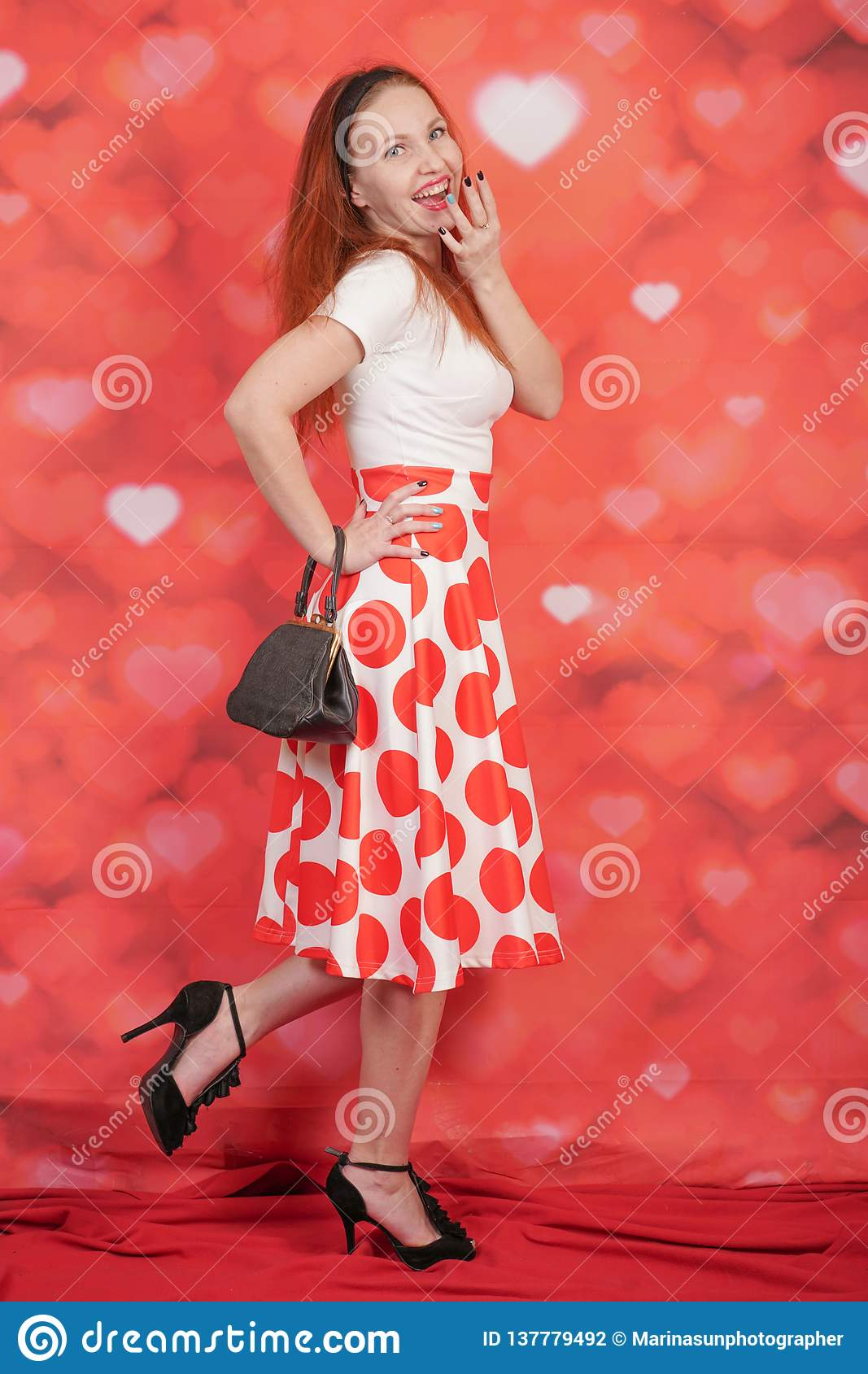 Pretty stylish pin up girl in white shirt and red polka dot vintage skirt standing on red hearts background