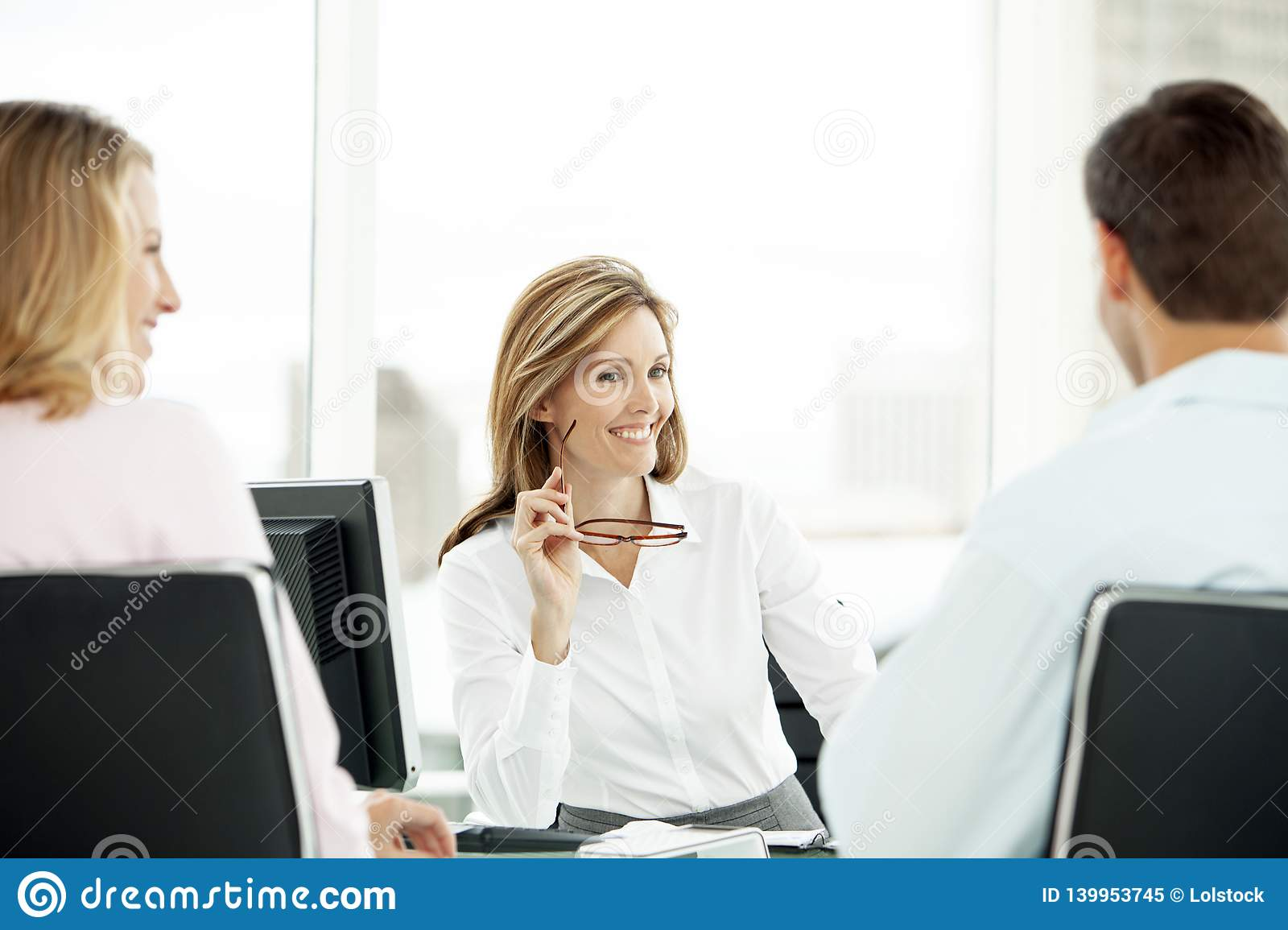 Financial advisor with couple at meeting in office - lawyer providing advice to man and woman - real estate agent with clients