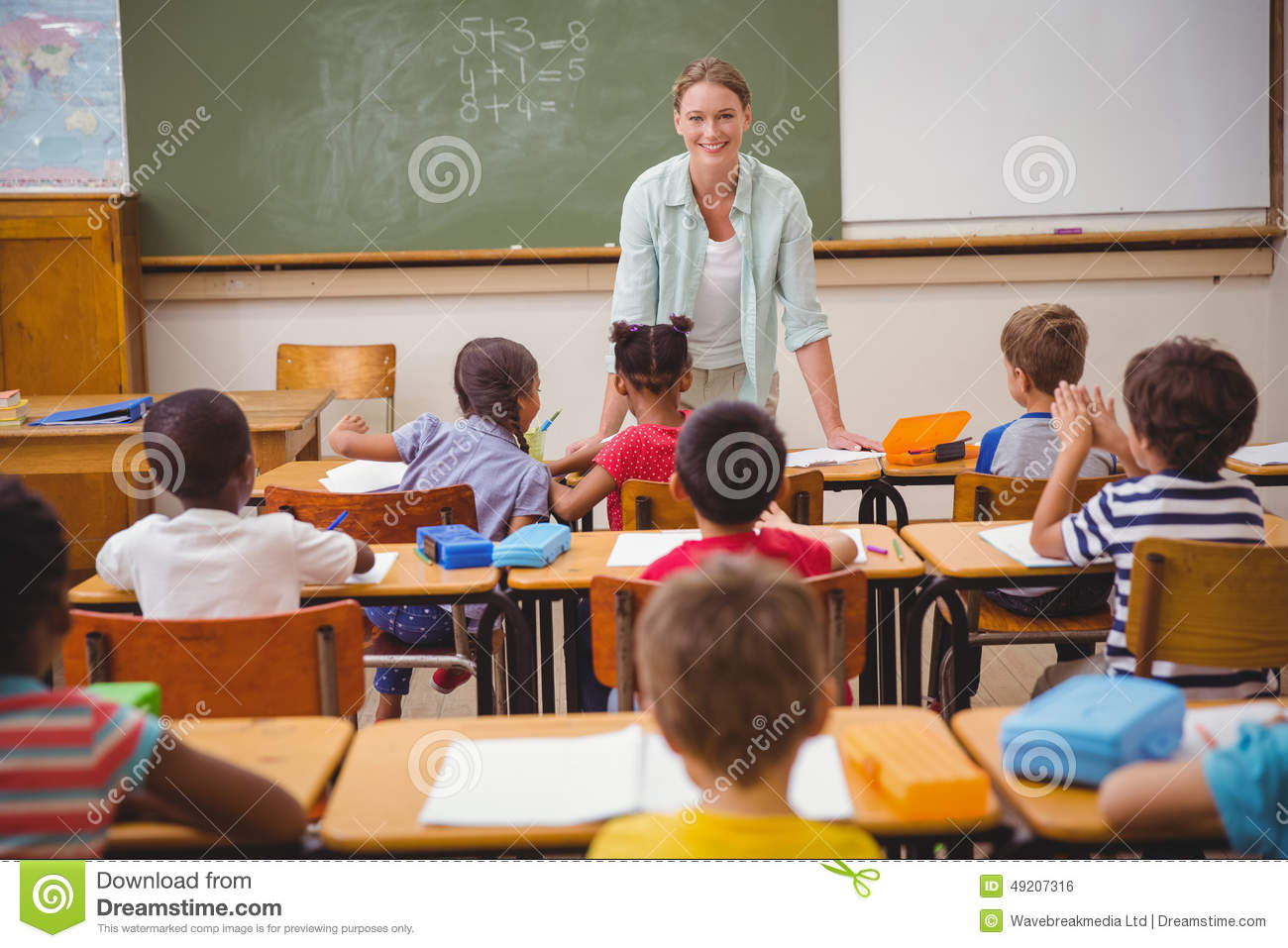 Pretty Teacher Talking To The Young Pupils In Classroom ...