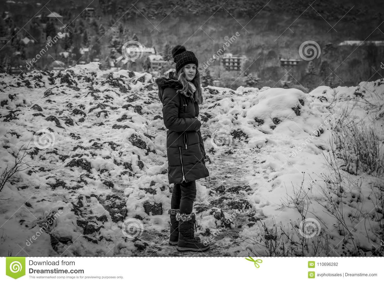 Pretty teen girl in snow facing camera black and white