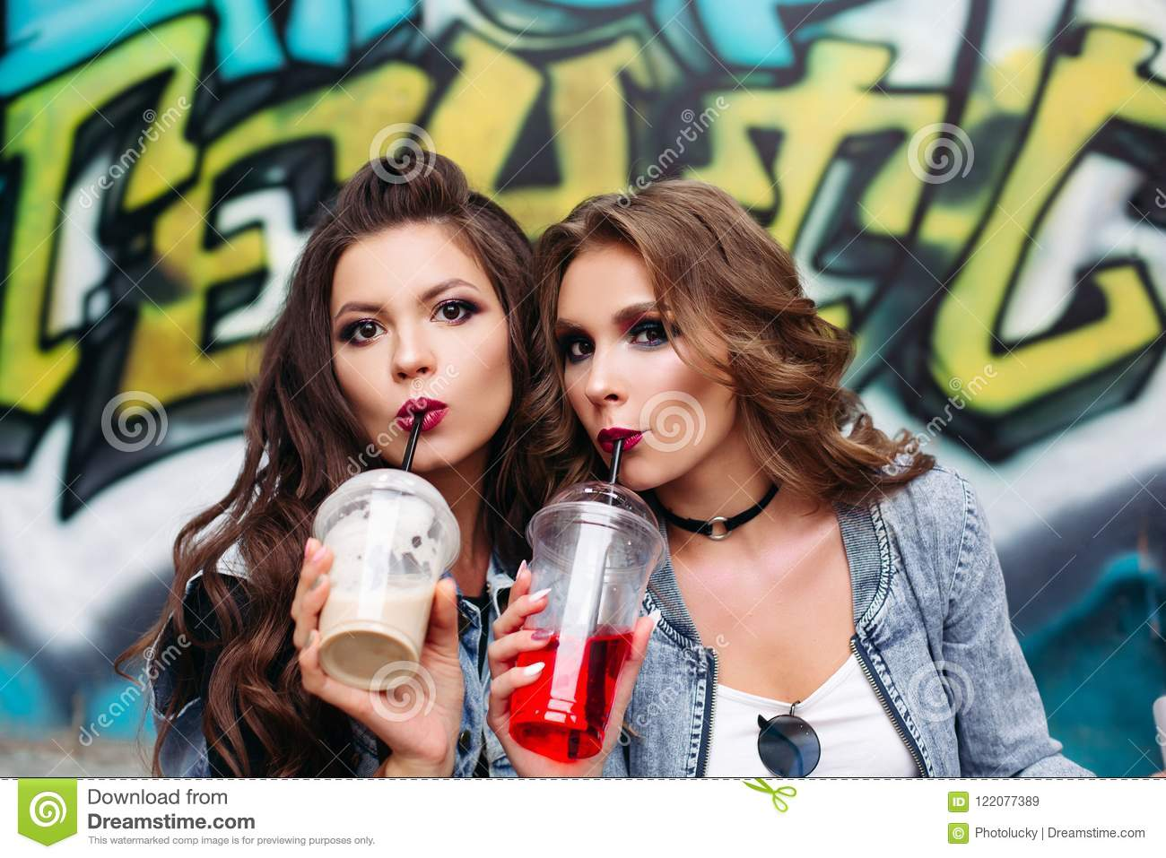 6743cff803400 Pretty teen girls with make up and hairstyle drinking takeaway lemonade  over graffiti.