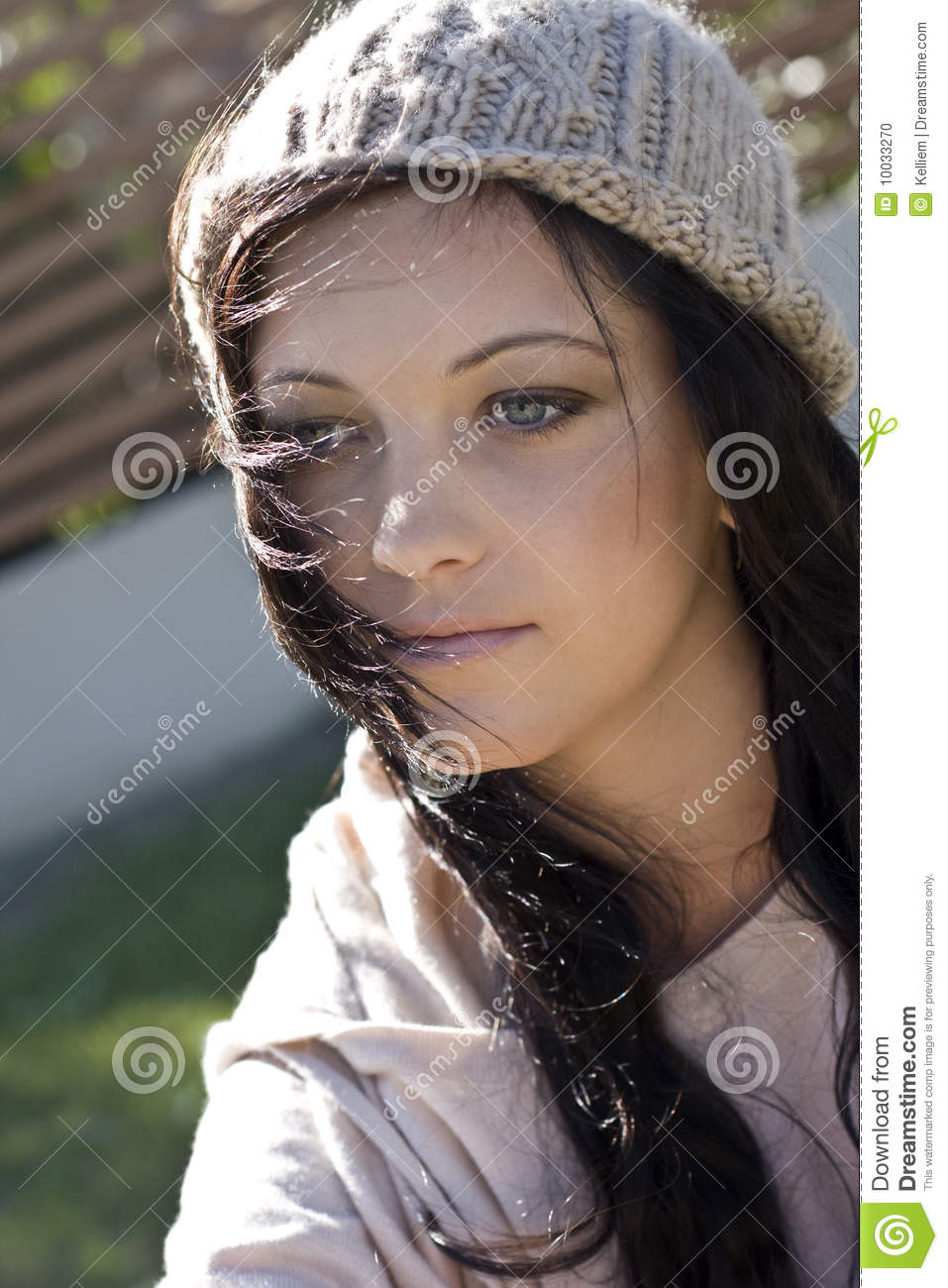An outdoor portrait of a young, pretty, teenage girl wearing a knit ...