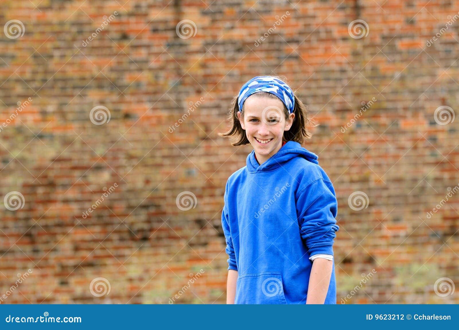 Pretty teenage girl against brick wall