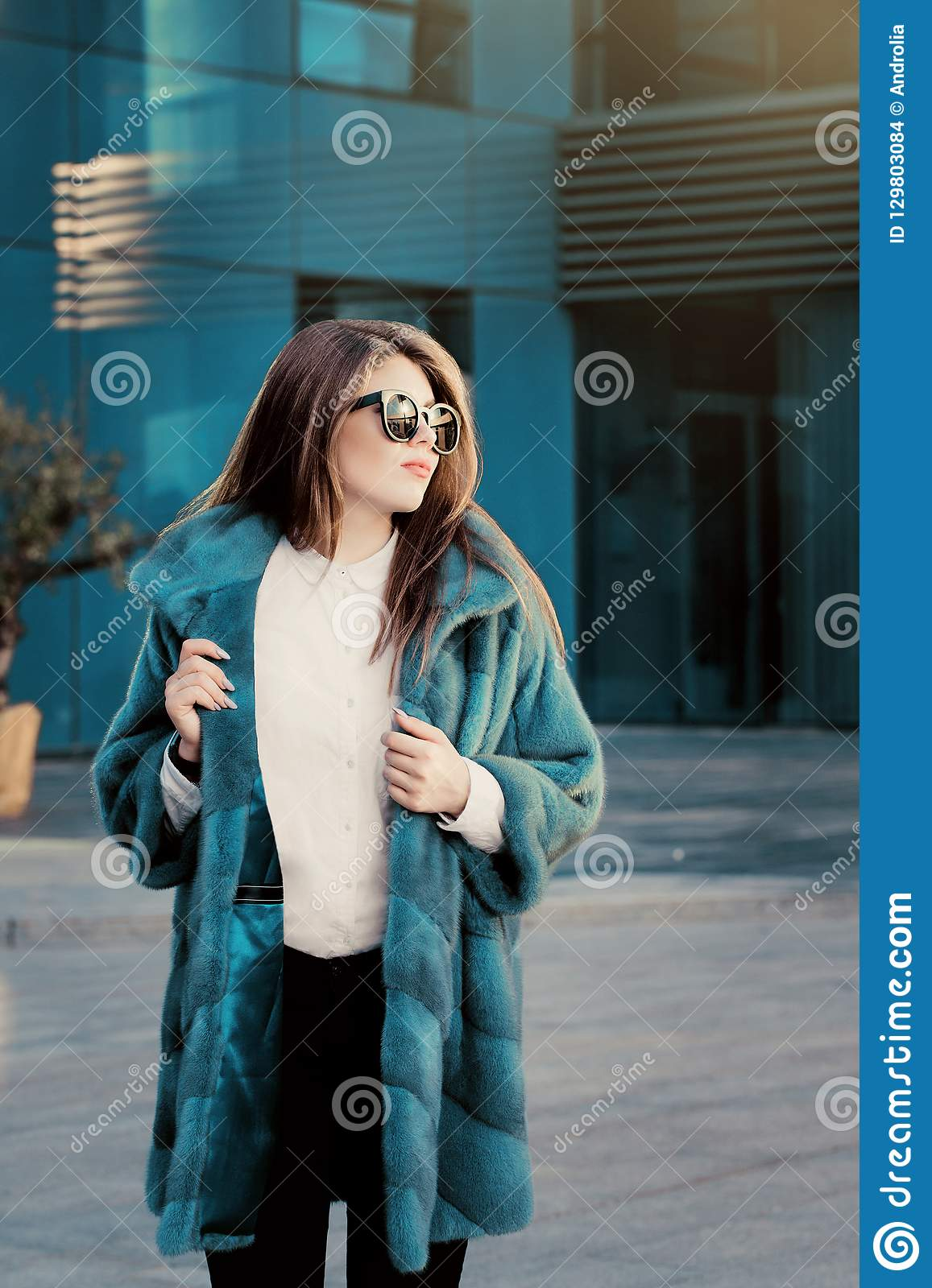 Pretty teenage girl in a bright colorful natural fur coat and sunglasses