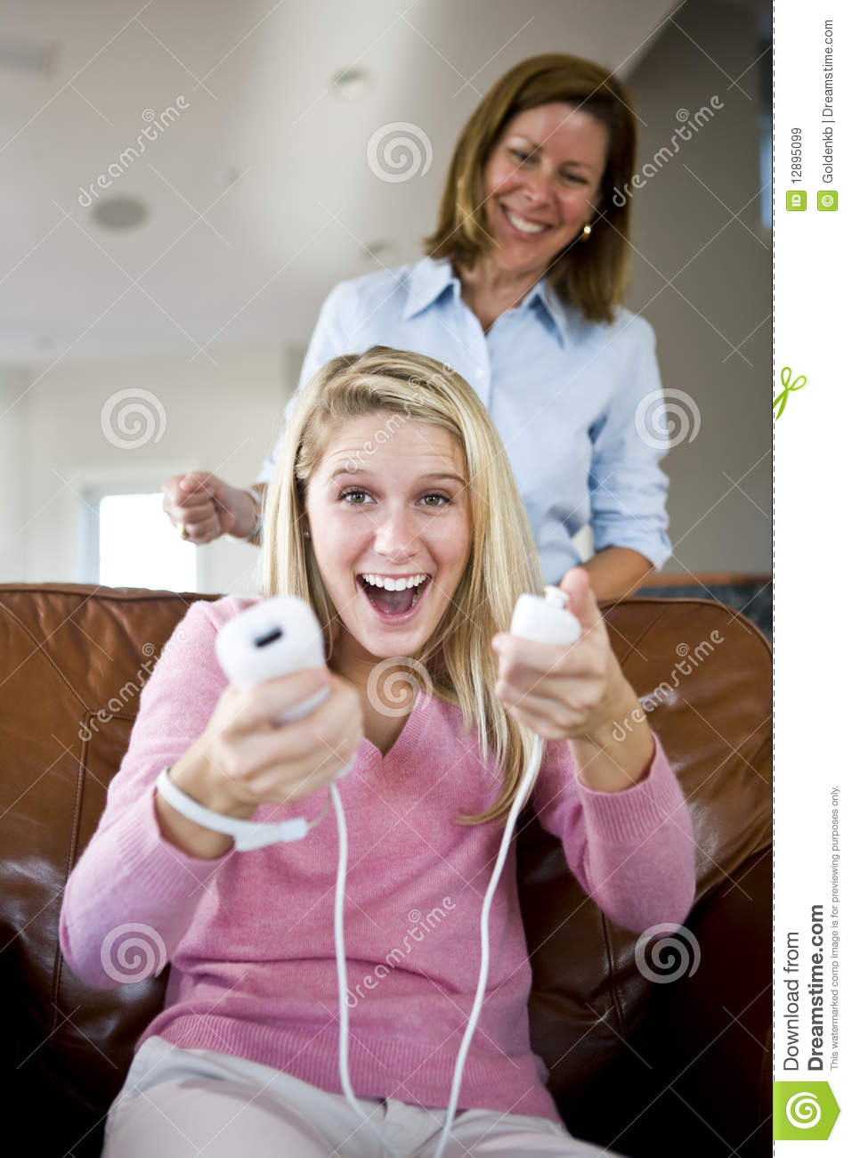 pretty teenage girl playing video games at home stock