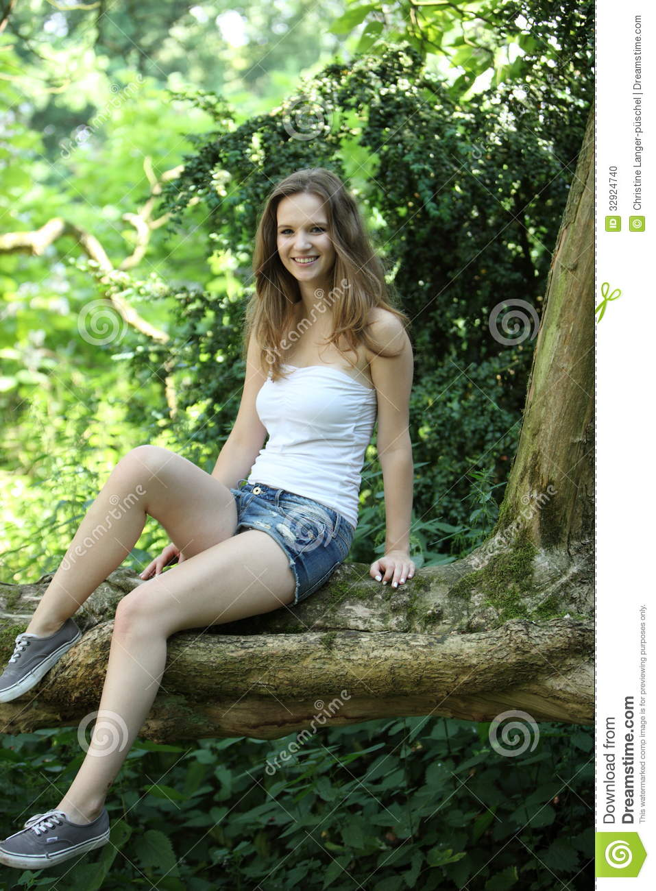 Pretty Teenage Girl Sitting On A Garden Wall Stock Photo
