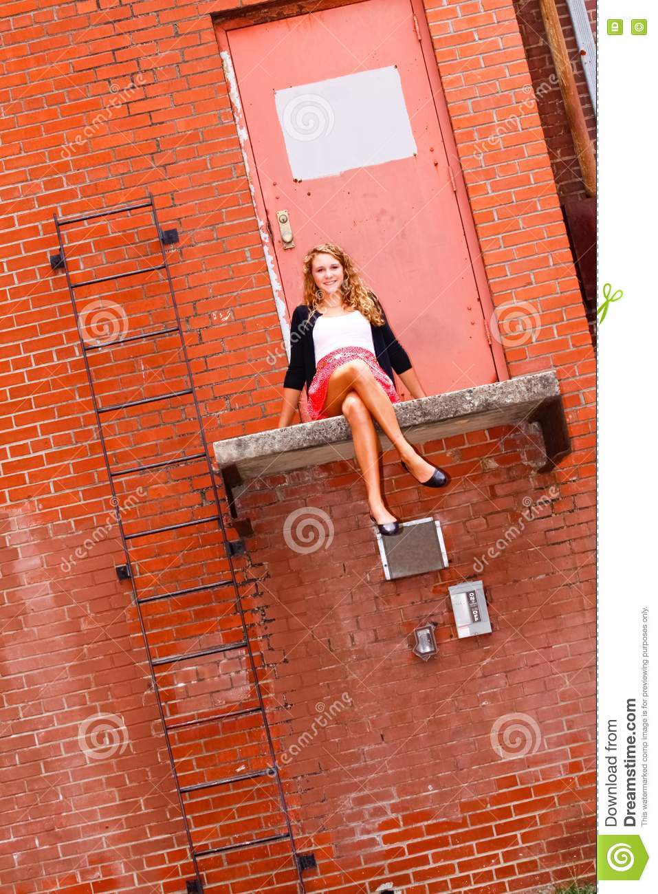 Black sweater sitting on a ledge in front of a red brick wall and door