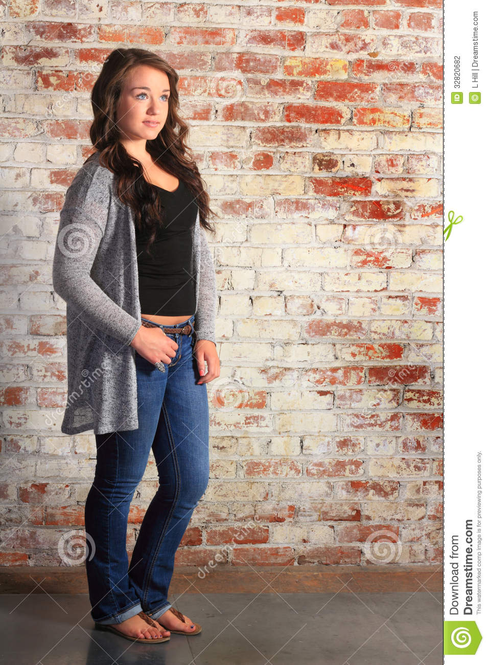 pretty typical teenage girl standing relaxed by a brick wall.