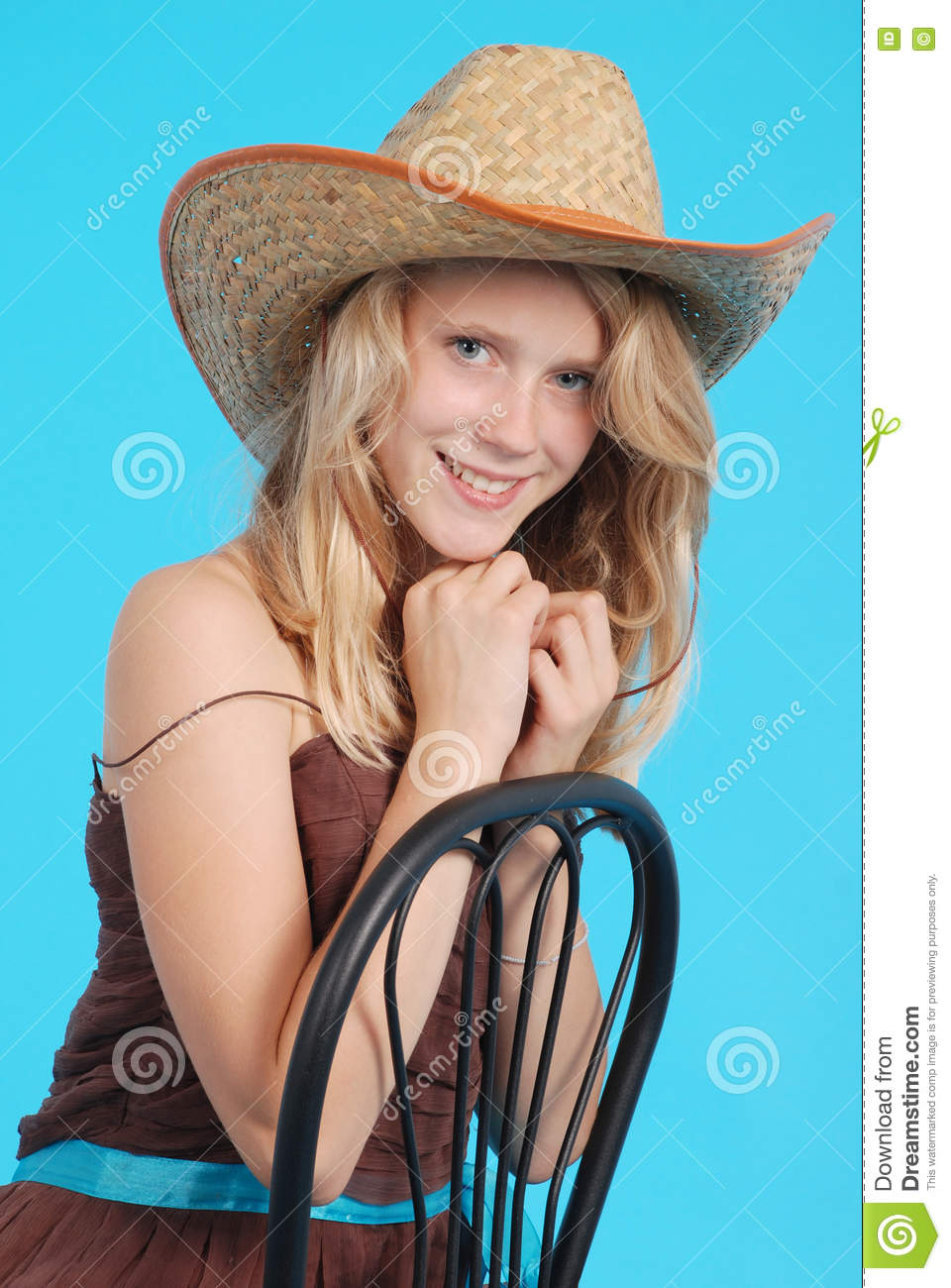 48977651a6e Pretty thirteen year old girls wearing a big floppy straw sun hat isolated  on blue