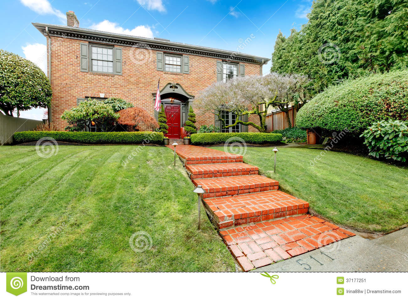 Pretty two story brick house with stoned walkway stock for Brick houses without shutters