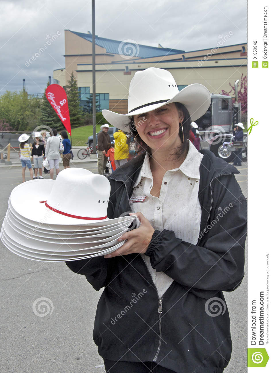 A pretty female volunteer smiles as she looks for people to give a free  white cowboy hat to at a Calgary Stampede Community Pancake breakfast. d94d8f65aac