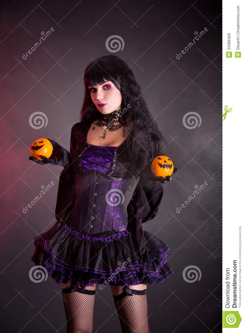 Pretty Witch With Halloween Styled Oranges Stock Photo