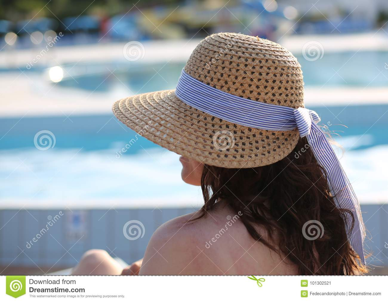 Pretty woman with a big straw hat and she relaxes in the exclusi