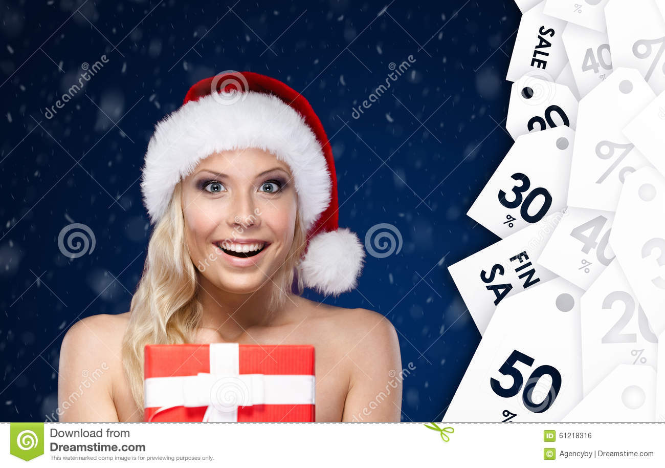 Pretty woman in Christmas cap hands present wrapped with red paper