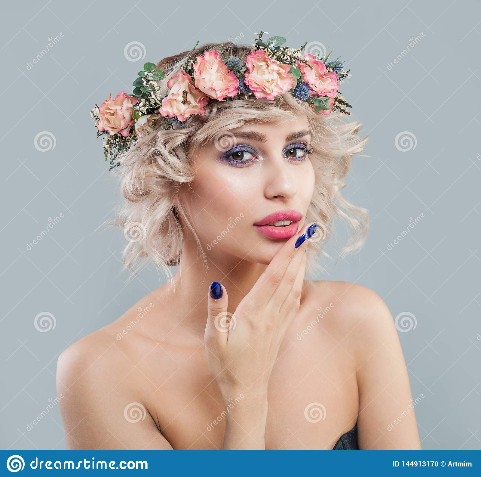 Pretty woman with clear skin, makeup, flowers and short curly haircut portrait