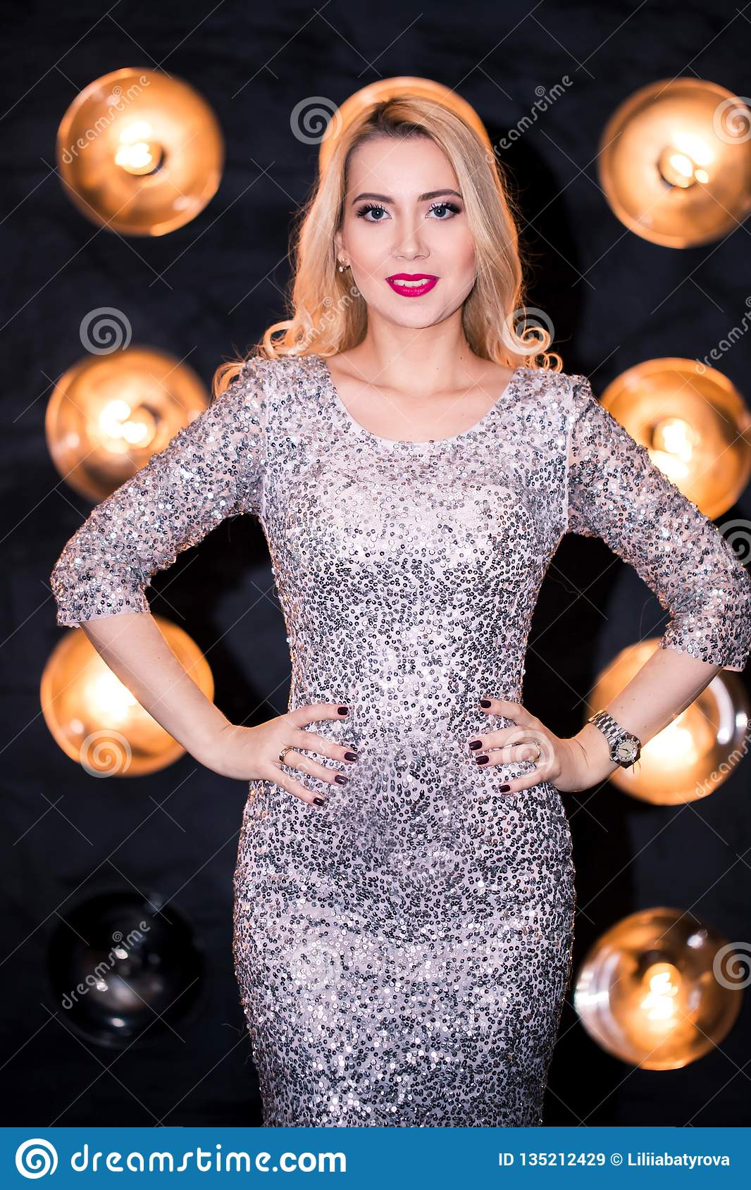 Pretty woman or cute girl in silver sequins dress and trendy makeup on face. party and holiday