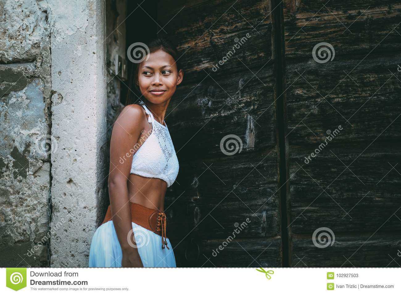 Pretty woman in ethnic Mediterranean traditional costume entering the wooden barn doors