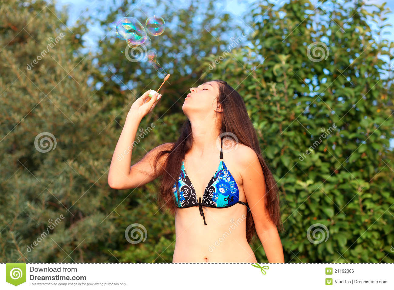 Pretty woman inflating soap bubbles