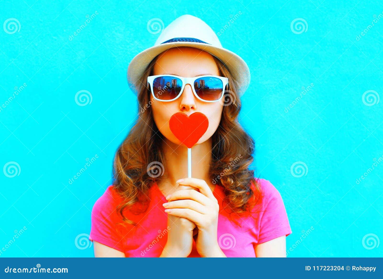 Pretty woman kissing red lollipop shape of a heart