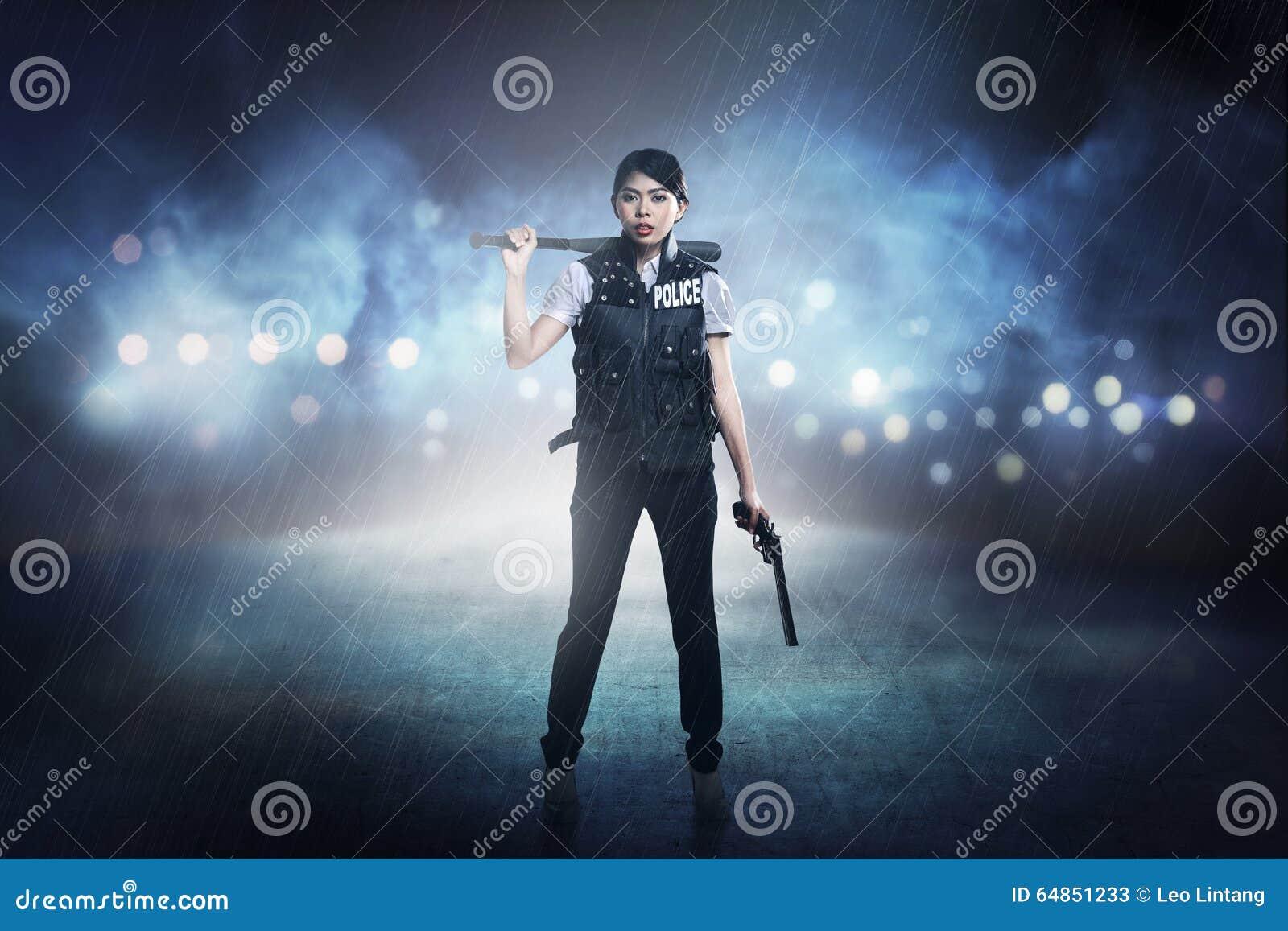 Pretty woman in police vest holding baseball bat