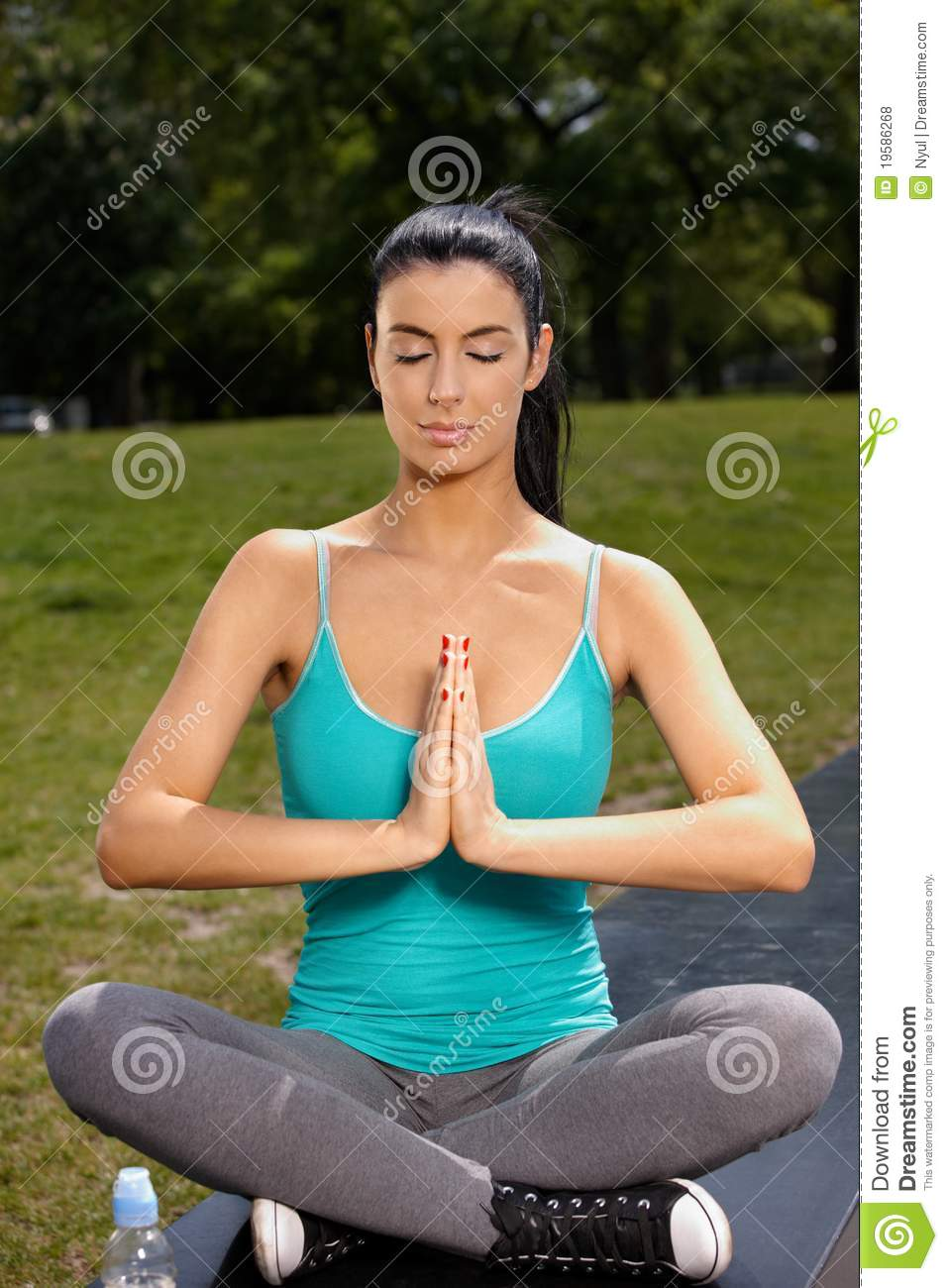 Pretty woman practicing yoga in park