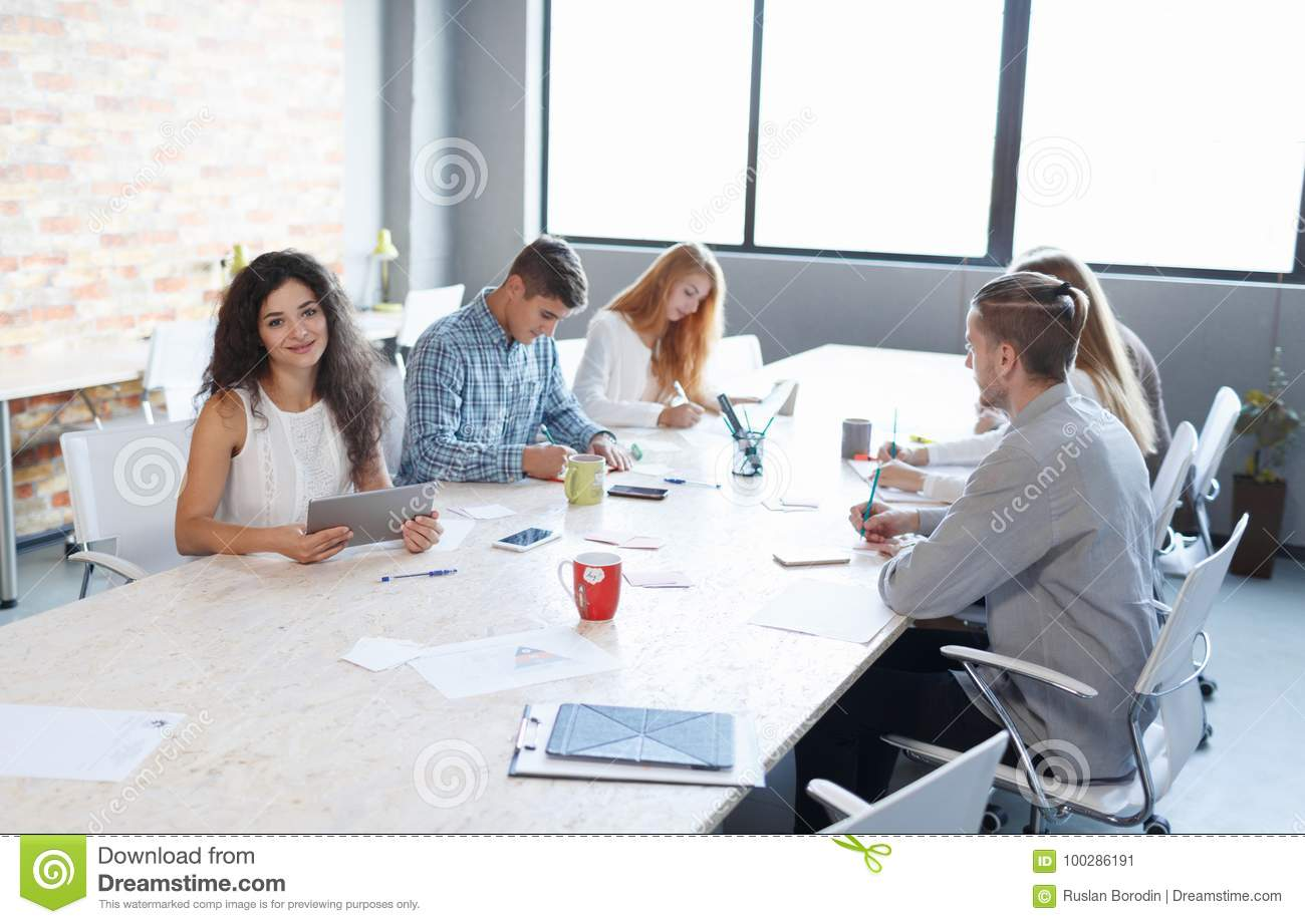 Pretty woman on a presentation with office staff on a meeting background. Partnership concept. Copy space.