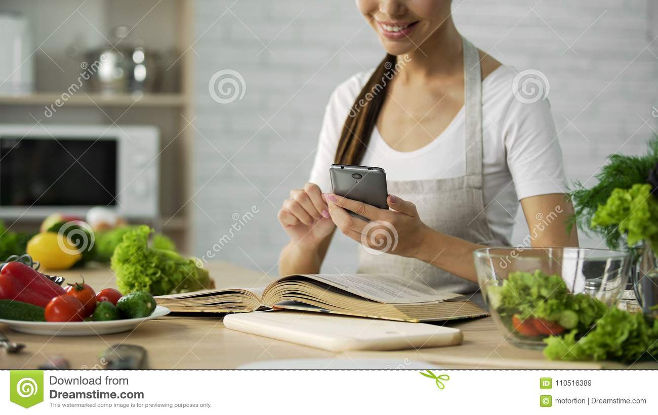 Pretty woman reading cooking book and calculating calories on smartphone app