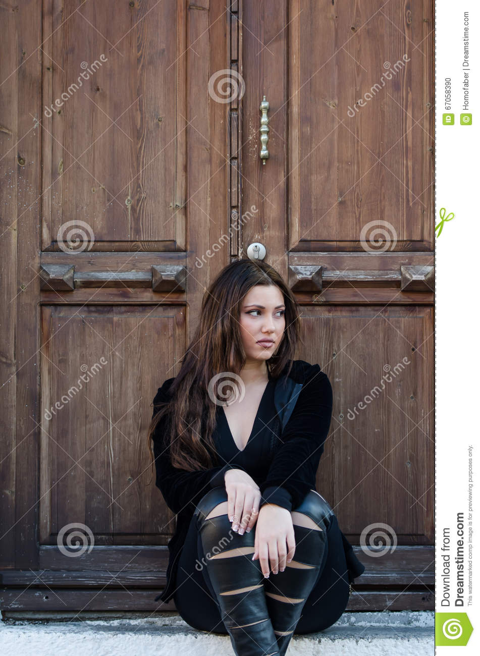 Pretty Woman Sitting On Stairs Front Of An Old Wooden Door