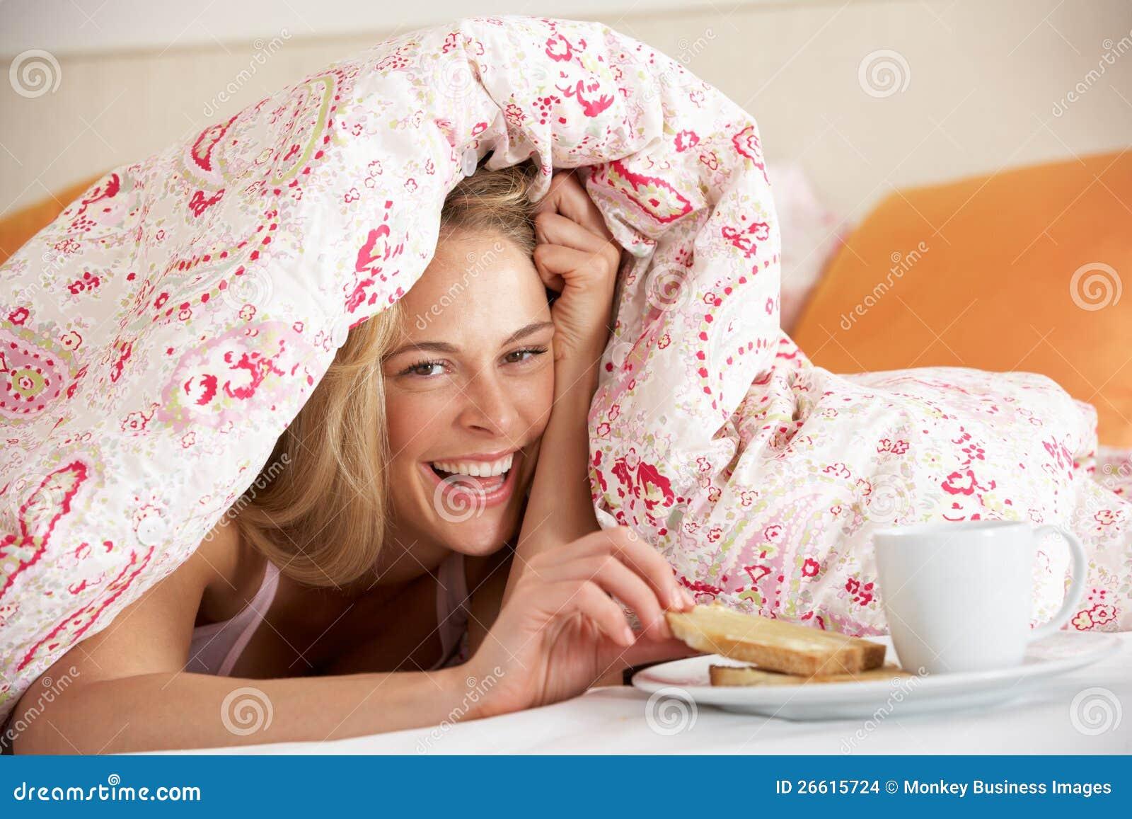 Man Snuggled Under Duvet Eating Breakfast Stock Photo