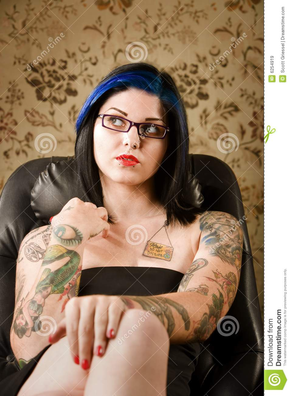 Pretty woman with tattoos in a leather chair stock image for Woman with tattoos