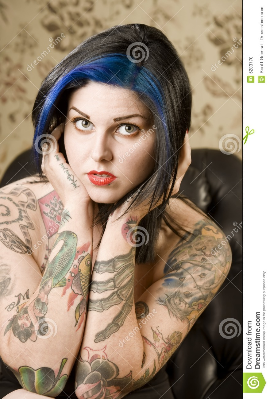 Pretty woman with tattoos in a leather chair stock photo for Woman with tattoos