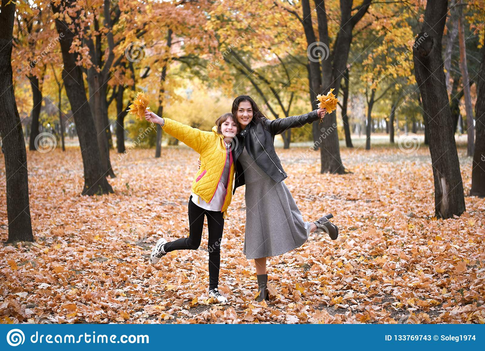 Pretty woman and teen girl are posing with bunch of maple`s leaves in autumn park. Beautiful landscape at fall season