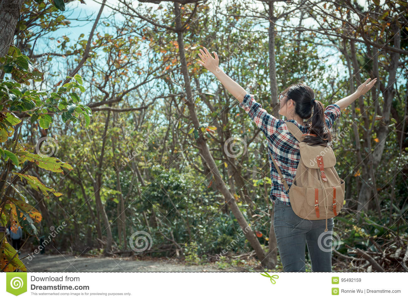 Pretty woman traveler standing in forest path