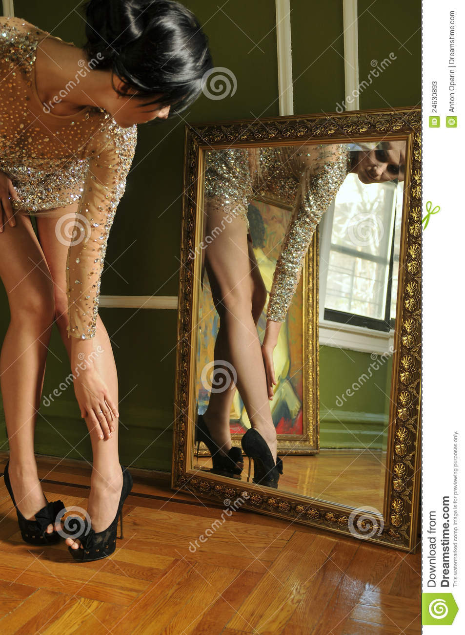 Pretty woman in vintage gown looking in the mirror