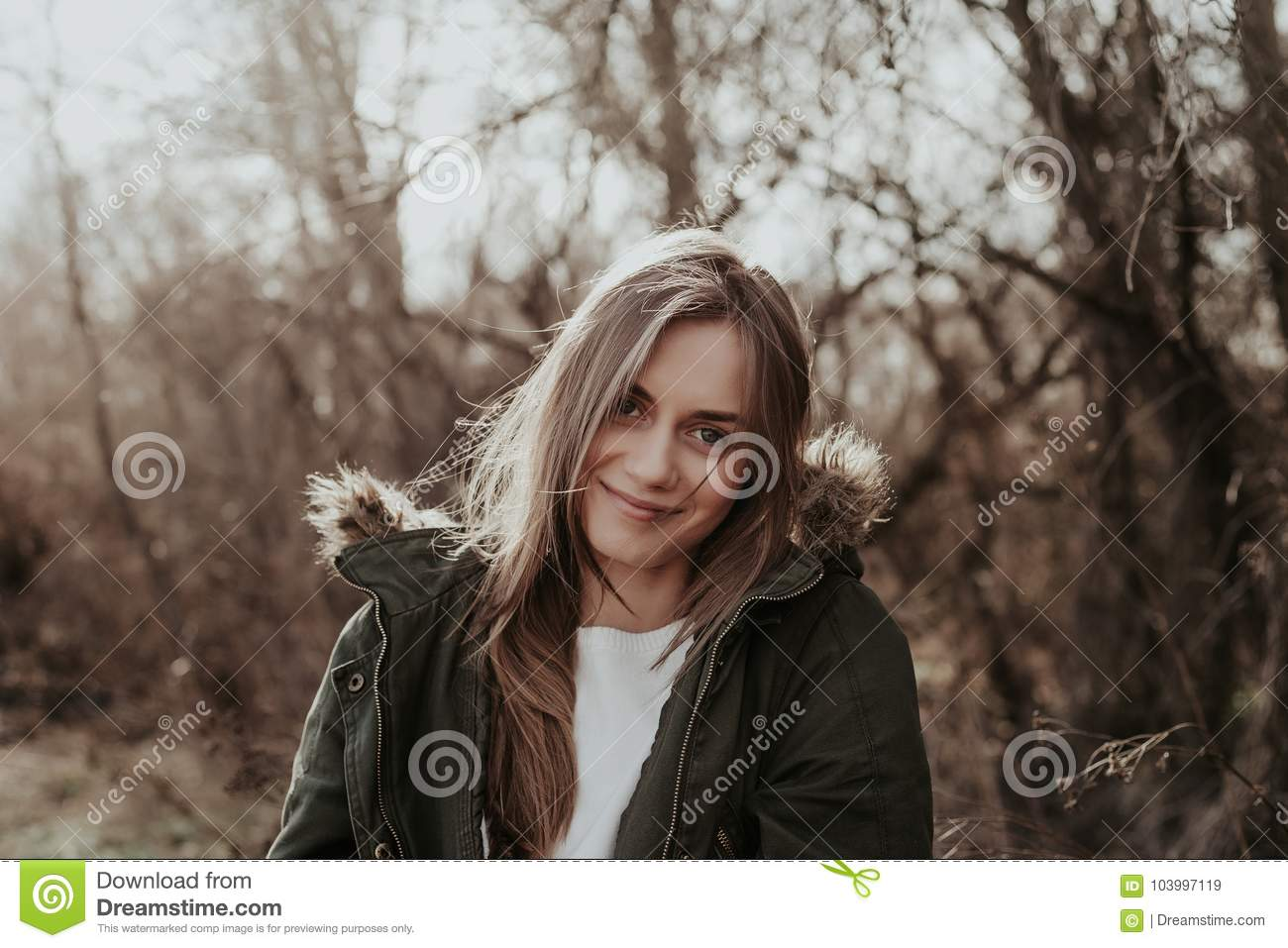 Pretty woman in warm jacket with fur posint at camera outdoor