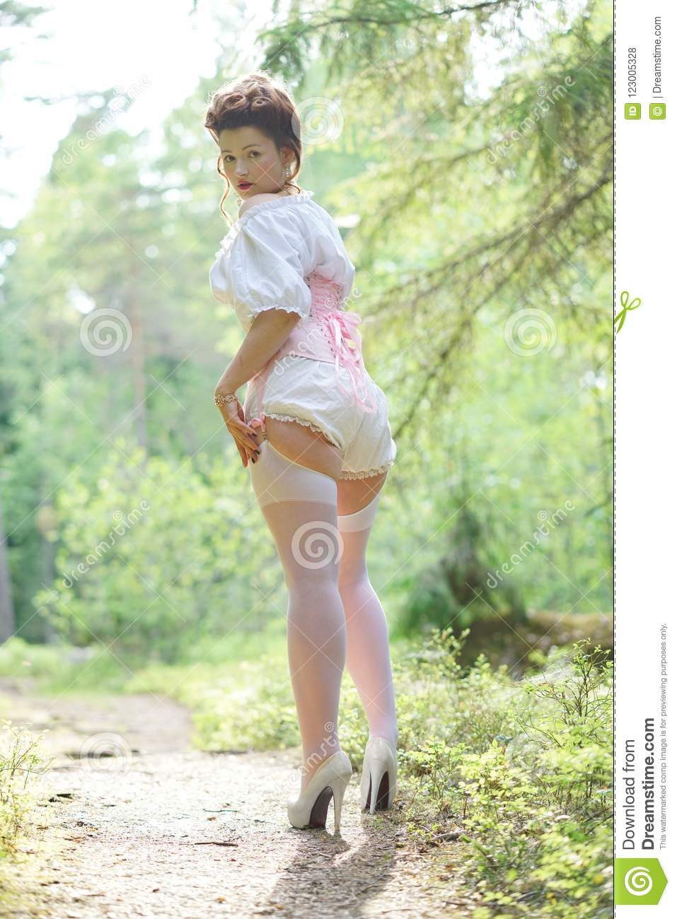 b3821f4d91 Beautiful young chubby girl posing in medieval retro corset and white  vintage lingerie in the forest