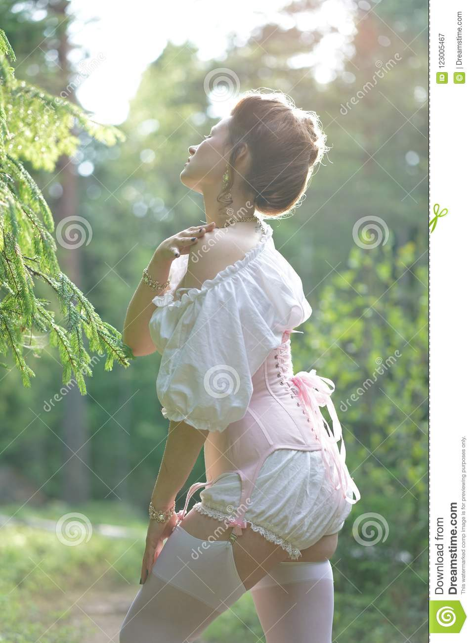 966c0cf8c01 Beautiful young chubby girl posing in medieval retro corset and white  vintage lingerie in the forest